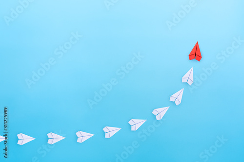 Fototapeta Leadership concept with red paper plane leading among white paper planes on blue background. copy space obraz na płótnie