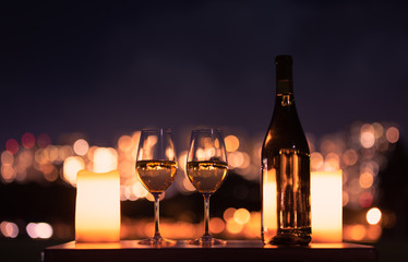 Candlelight dinner with wine and romantic city view.