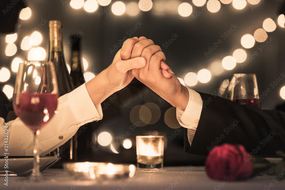 Fototapeta Couple enjoying a romantic candle light dinner date.