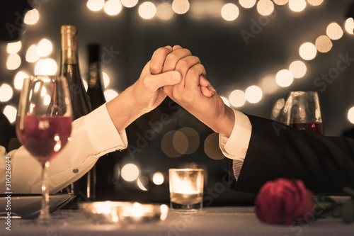 Fototapeta Couple enjoying a romantic candle light dinner date.  obraz