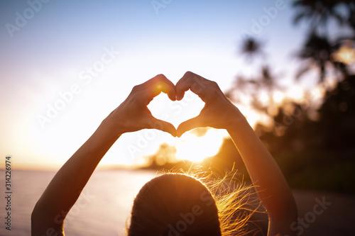 Fotografia, Obraz Female making a heart shape on the beach at sunset
