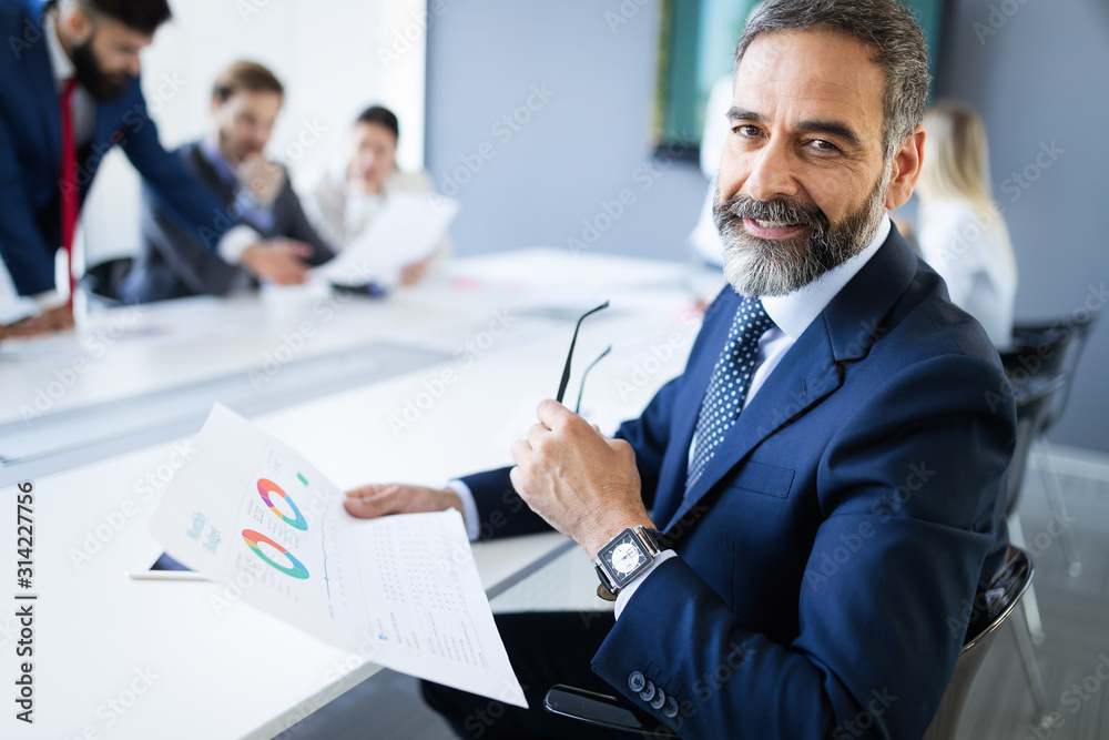 Fototapeta Confident senior businessman leader working in office