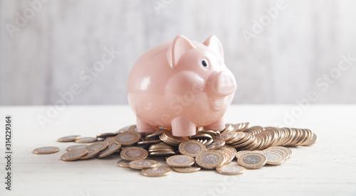 Fotografía Piggy bank with coins on the desk. Saving money
