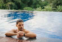 An Attractive Sporty Man In An Outdoor Pool Looks At The Smartwatch Tracker After An Active Swim.