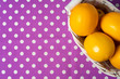 canvas print picture - Basket of lemons on dotted purple tablecloth