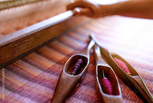 Kobieta pracuje na maszynie do tkania tkaniny ręcznie tkane. Tkactwo tekstylne. Tkanie przy użyciu tradycyjnego krosna ręcznego na niciach bawełnianych Produkcja tkanin lub sukna w Tajlandii. Kultura azjatycka.