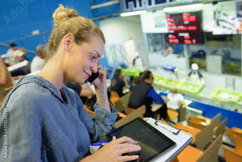 Photo female bidder using tablet in auction hall