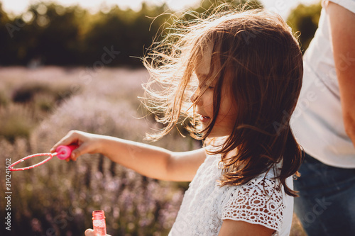 Valokuvatapetti Side view portrait of a charming little girl doing soap balloons smiling against sunset in a field of flower while wind blowing her hair