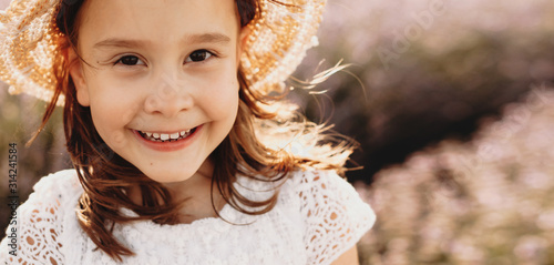 Close up portrait of a lovely little girl looking at camera laughing while wearing a hat against sunset in a field of flowers while wind in blowing her hair Canvas-taulu