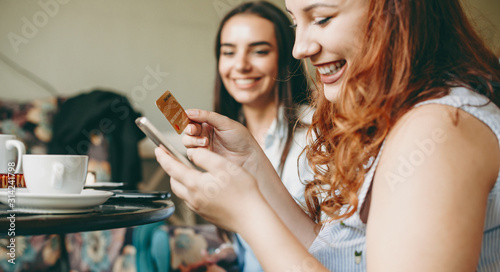 Portrait of a charming plus size women using a smartphone and a gold credit card smiling while sitting in a restaurant Canvas Print