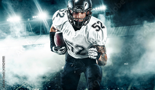 American football player. Sportsman with ball in helmet on stadium in action....