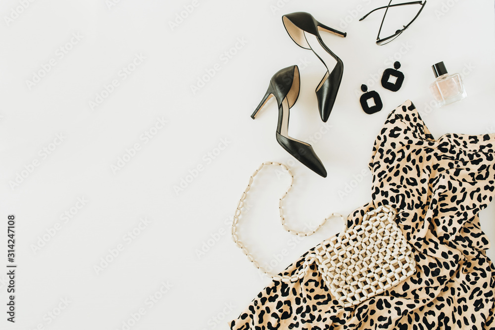 Fototapeta Modern fashion collage with female clothes and accessories. Leopard print dress, high-heel shoes, earrings, glasses, purse, perfume on white background. Flat lay, top view.