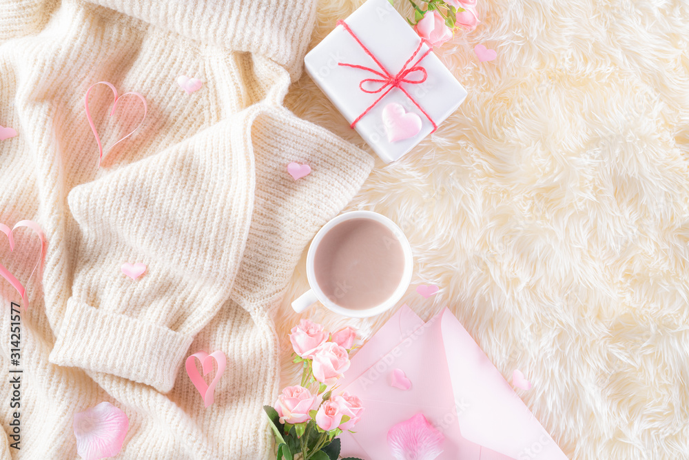 Fototapeta Pink paper hearts with gift box and roses, coffee cup on , beige sweater on cream colour knitted blanket and fluffy background. Love and Valentine's day during Winter concept.