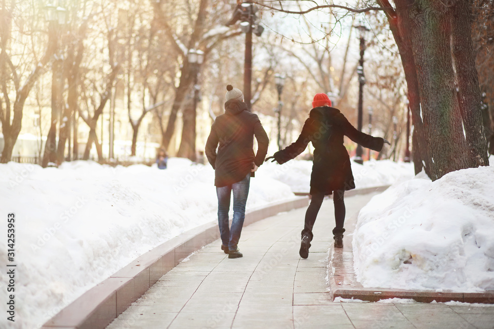 Fototapeta Young couple walking through the winter