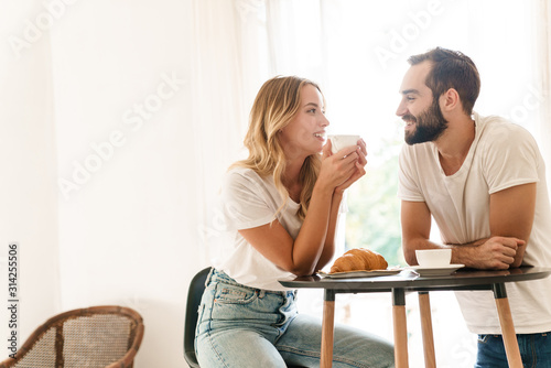 Fototapeta Happy beautiful young couple having breakfast at the kitchen table obraz