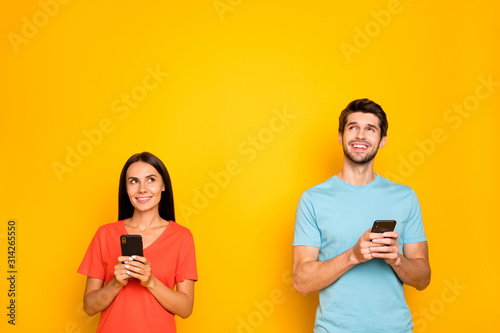 Fototapeta Photo of two funny guy lady people couple hold telephones arms looking up empty space have creative post text idea wear casual blue orange t-shirts isolated yellow color background obraz