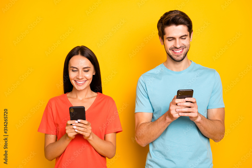 Fototapeta Photo of two funny guy lady people couple hold telephones arms interested reading social network article wear casual blue orange t-shirts isolated yellow color background