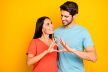 Photo Of Amazing Two People Guy Lady Celebrating Valentine Day Holding Fingers Heart Figure Shape Looking Eyes Wear Casual Blue Orange T-shirts Isolated Yellow Color Background