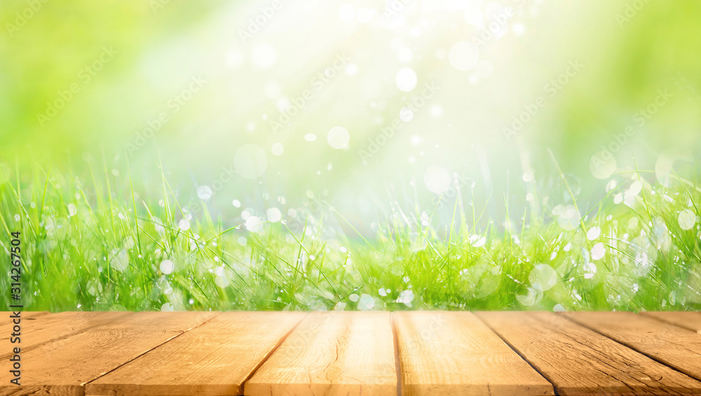 Fototapeta Beautiful spring natural  background with green fresh juicy young grass and empty wooden table in nature morning outdoor.  Beauty bokeh and sunlight.