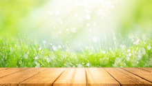 Beautiful Spring Natural  Background With Green Fresh Juicy Young Grass And Empty Wooden Table In Nature Morning Outdoor.  Beauty Bokeh And Sunlight.
