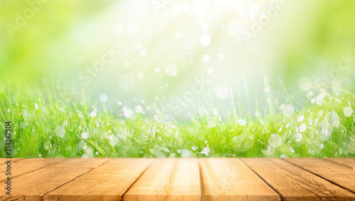 Fototapeta Beautiful spring natural  background with green fresh juicy young grass and empty wooden table in nature morning outdoor.  Beauty bokeh and sunlight. obraz