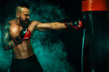 Boxer Fighting In Gloves With Boxing Punching Bag. Sportsman With Tattoos, Man Isolated On Black Background With Smoke. Copy Space.