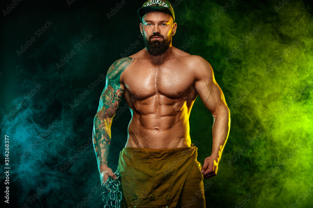 Fototapeta Gay streptizer with naked torso. Muscular fitness sports man, atlete with chains in fitness gym. Energy and power.