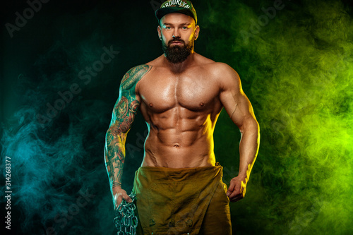 Obraz Gay streptizer with naked torso. Muscular fitness sports man, atlete with chains in fitness gym. Energy and power. - fototapety do salonu