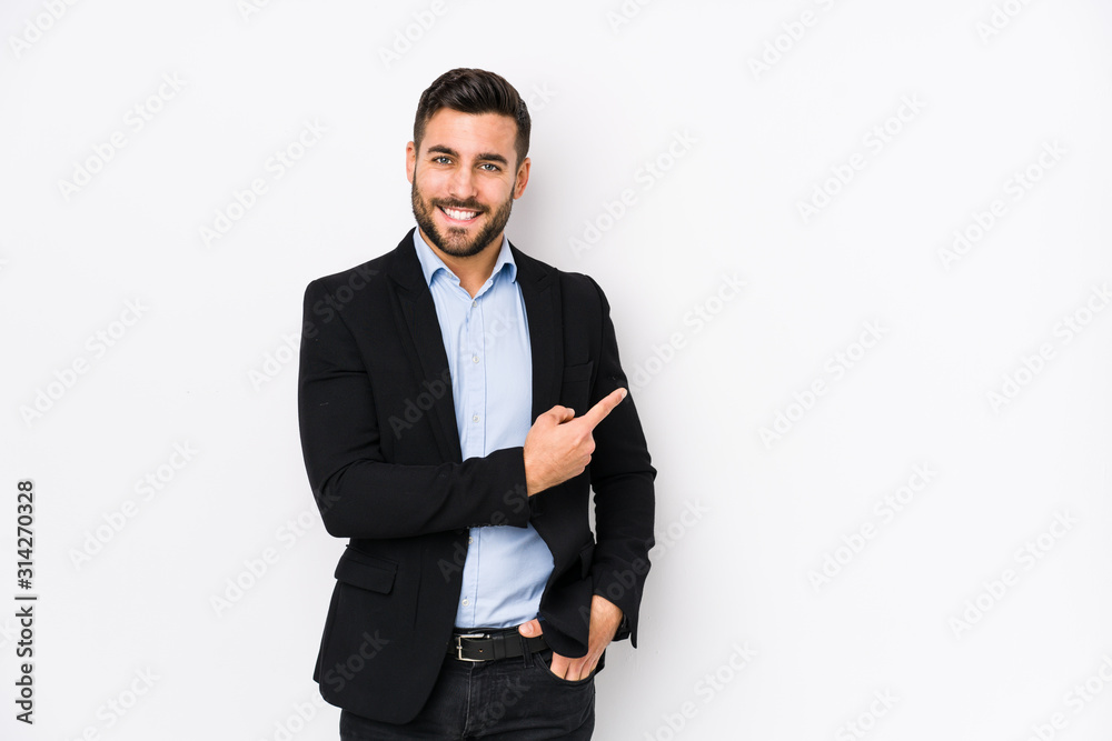Fototapeta Young caucasian business man against a white background isolated smiling and pointing aside, showing something at blank space.