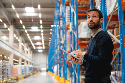 Obraz Manager holding digital tablet in warehouse - fototapety do salonu