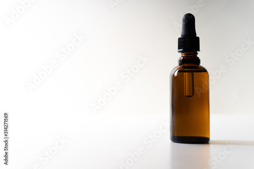 Fototapeta A small bottle with a dropper full of CBD oil or any other oil on white background obraz