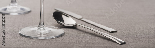 Spoon and knife near wine glasses on grey surface, panoramic shot