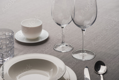 Clear wine glasses beside dishware and coffee cup on grey cloth