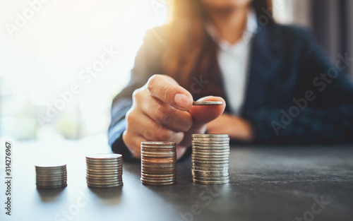 Fotografía Businesswoman holding and stacking coins on the table