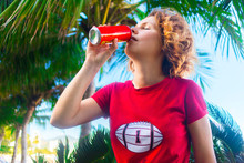 Beautiful Gorgeous Girl Drinking Soda Cold Coca Cola From Can In Red T-shirt With Ball For American Football. Young Woman Thirsty, Wants To Drink With Summer Background With Palms, Clear Sky, Beach.
