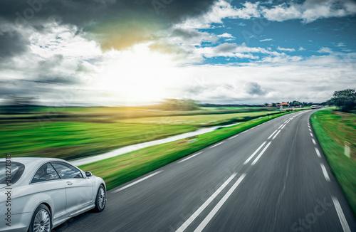 Obraz A white car on a country road. - fototapety do salonu