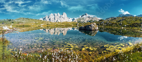 Wall mural - Wonderful Alpine Scenery. Incredible Dolomites Alps In Sunny Day. Awesome Alpine highland with Lake in spring. Impessive Nature Landscape of Tre Cime di Lavaredo Park. Italy. Natural Bacground