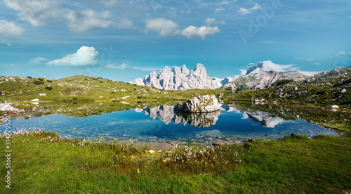Wall mural - Wonderful picturesque Scenery of Dolomites Alps. Beautiful Lake with flowers on shore and Majestic Mountains Range with perfect sky in background. Tre Cime di Lavaredo national park. Dolomite. Italy