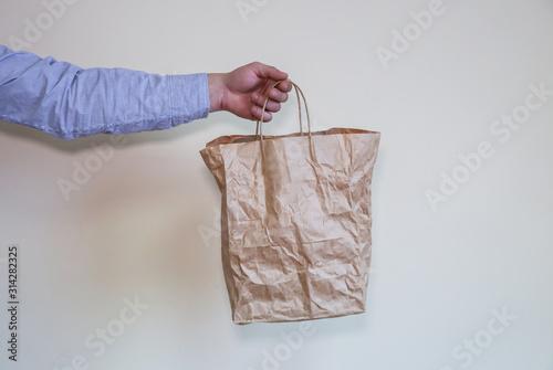 Fototapety, obrazy: Man holds eco bag from kraft paper.