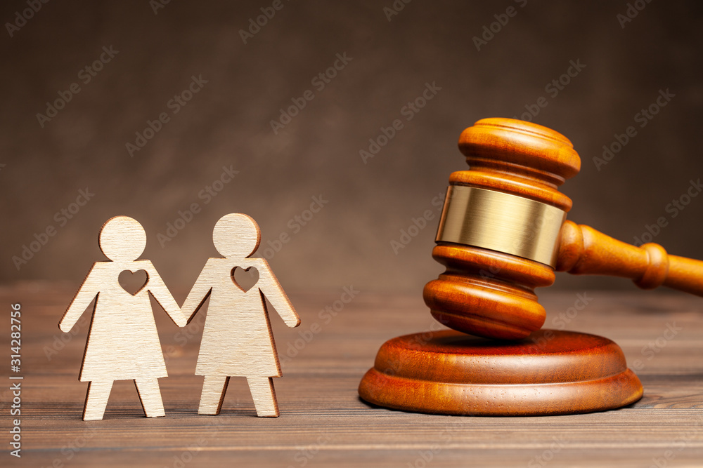 Fototapeta Illegal gay marriage. Two lesbians on the background of the judge's hammer. Law and marriage of same-sex people.