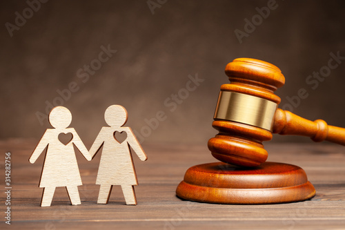 Fototapeta Illegal gay marriage. Two lesbians on the background of the judge's hammer. Law and marriage of same-sex people. obraz