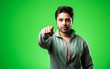 Leinwandbild Motiv satisfied Indian Man presenting, pointing, displaying or advertising with empty hands or fingers. standing isolated over green background
