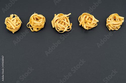 Fotografia  Italian tagliatelle pasta on a black background