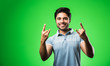 Leinwandbild Motiv Indian handsome man with success gesture, standing isolated over green background
