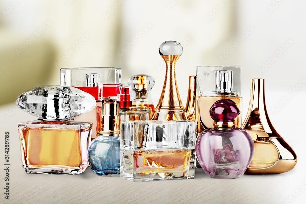 Fototapeta Aromatic Perfume bottles on white wooden desk at wooden background
