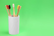 canvas print picture - Bamboo toothbrushes in holder on green background, space for text