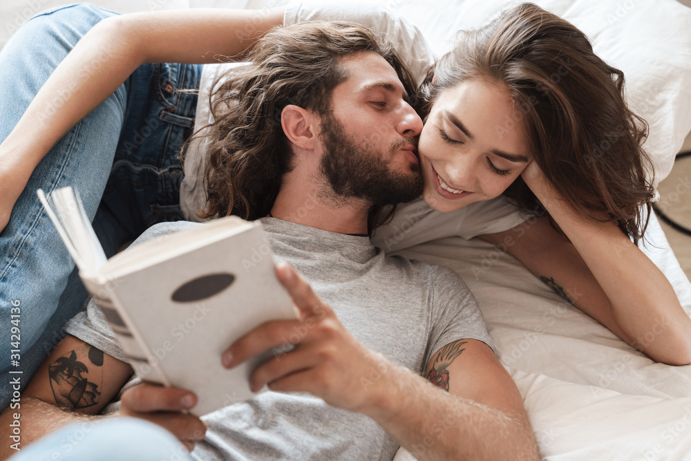 Fototapeta Loving couple indoors at home lies reading book together.
