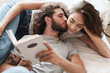 canvas print picture - Loving couple indoors at home lies reading book together.