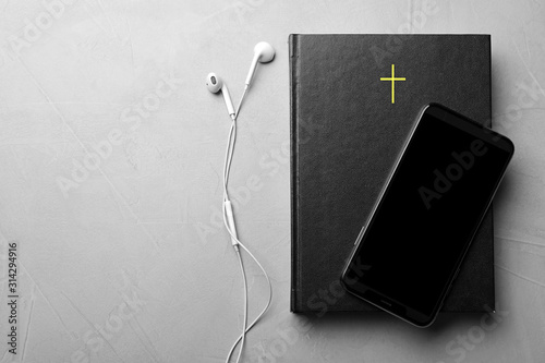 Fotomural Bible, phone and earphones on light grey background, flat lay with space for text