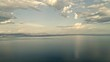 Scenic, picturesque aerial video of Mediterranean sea in the summer with beautiful clouds reflecting in the water and mountains on the horizon.